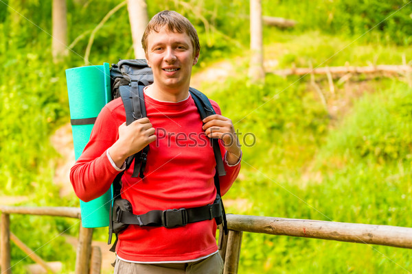 happy man with a backpack hiking in the summer forest