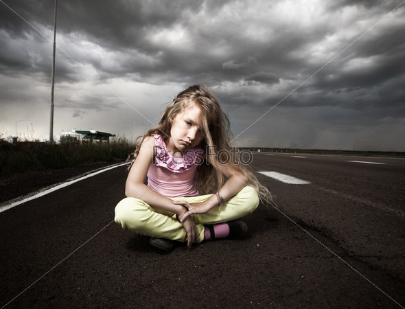 Sad child near road