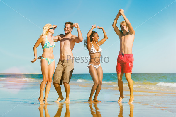 Friends jumping on ocean beach in vacation