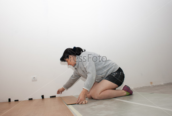 beautiful woman puts laminate flooring