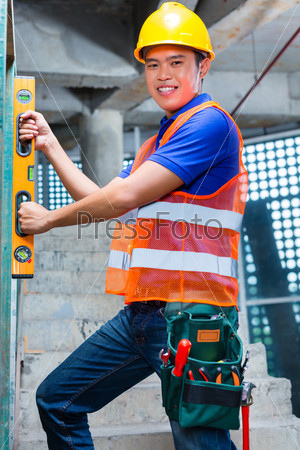 Builder or worker controlling wall on construction site