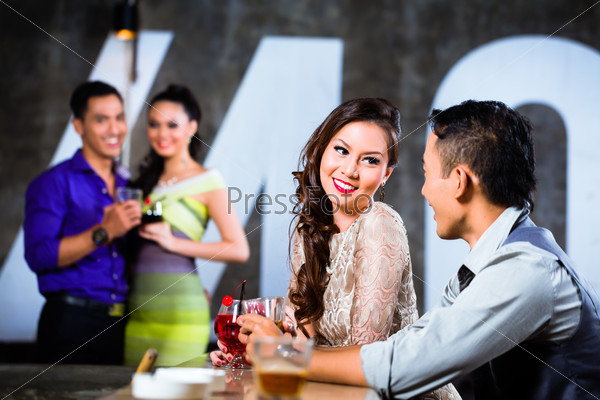 Asian couples flirting and drinking at nightclub bar