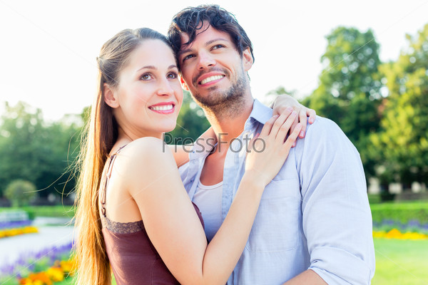 Tourist couple in city park hugging in love