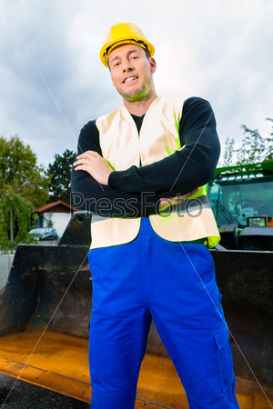 Builder on site in front of  construction machinery