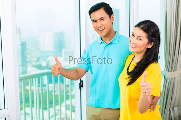 Asian couple looking out of apartment window