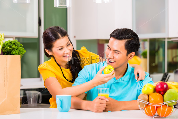 Asian woman feeding boyfriend with apple
