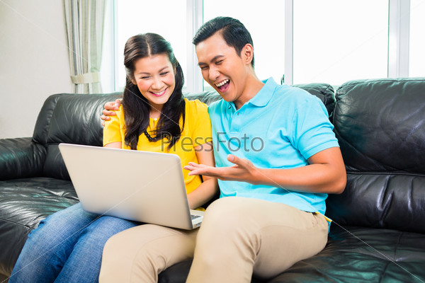 Asian couple using laptop on sofa