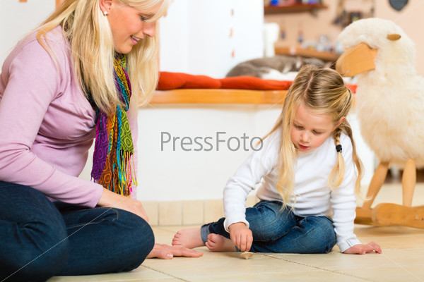 Girl playing with wooden toy spinner