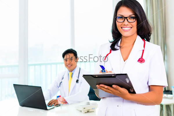 Asian doctor and nurse in surgery or office
