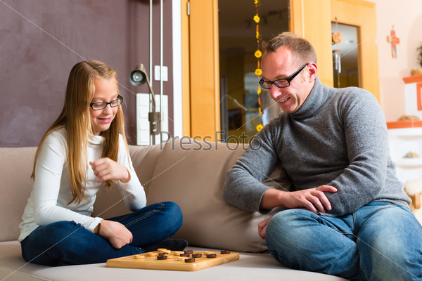 Father and daughter playing checkers