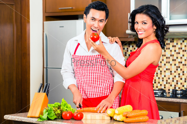 Asian couple preparing food in domestic kitchen