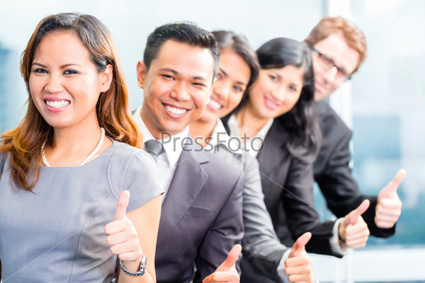 Asian business people standing in row in office