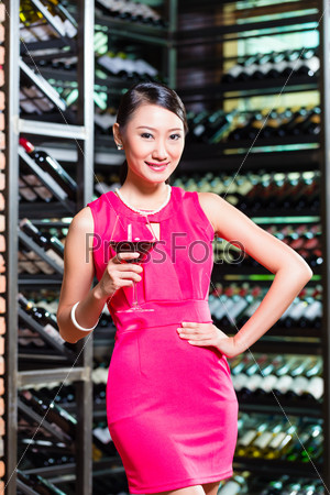 Asian woman holding glass of wine