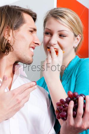 Couple eating grapes at home