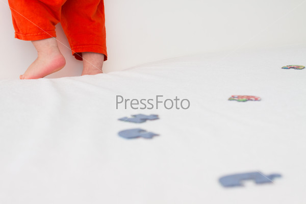 Child's legs, which stands on the bed