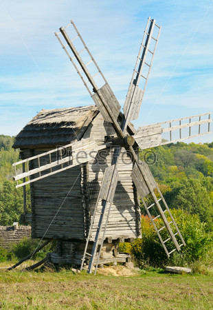 wooden windmill against the blue sky