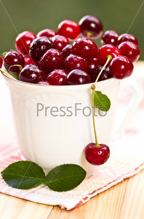 Cherry in a glass on a wooden table