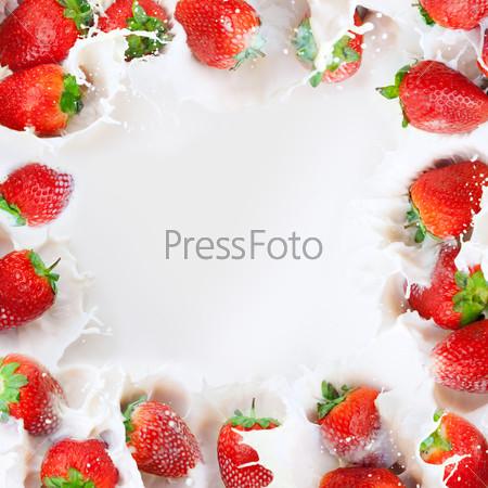Strawberries splashing into milk frame
