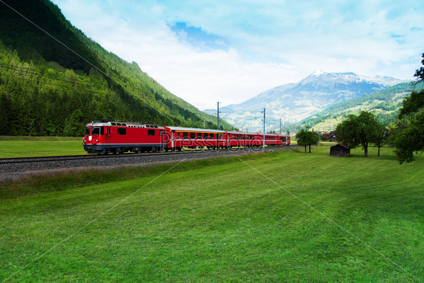 Red train crossing green valley near Alps