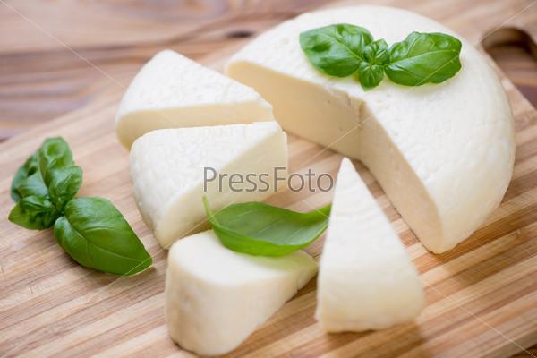 Адыгейский сыр и листья зеленого базилика