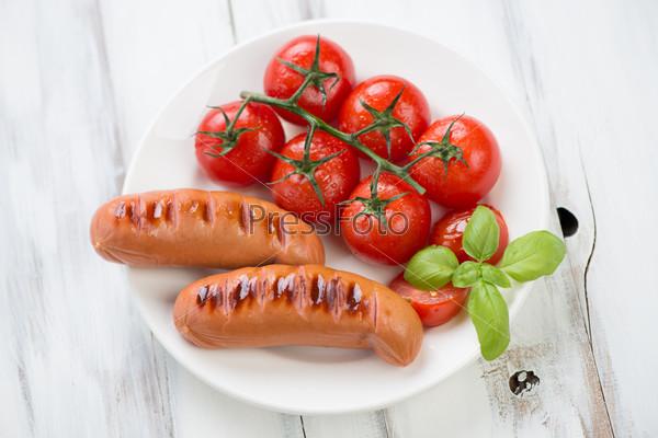Жареные сосиски и жареные красные помидоры