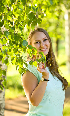 Young girl in a summer park birch