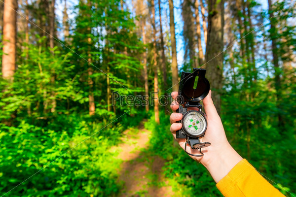 female hand holding a compass in the forest