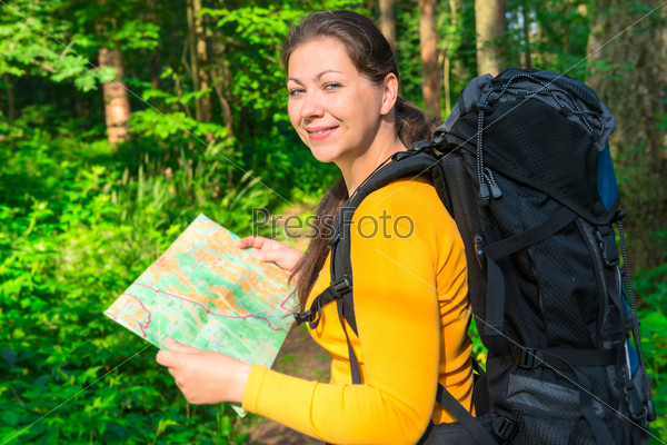 happy traveler with a map in the forest