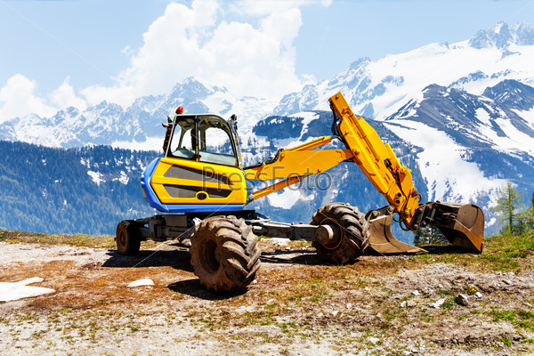Yellow excavator working near mountains