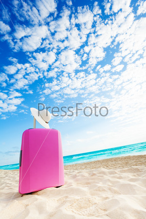 Cute pink baggage bag on the beach