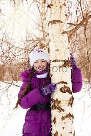 Happy girl hugging tree