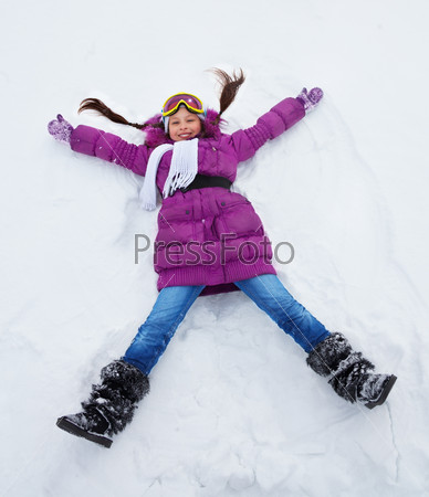 Girl laying in star shape in snow