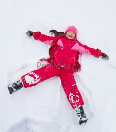 Little girl laying in star shape in snow