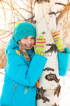 Happy girl hugging tree