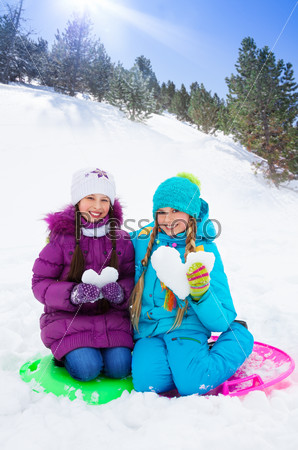 Two girls with snow hearts