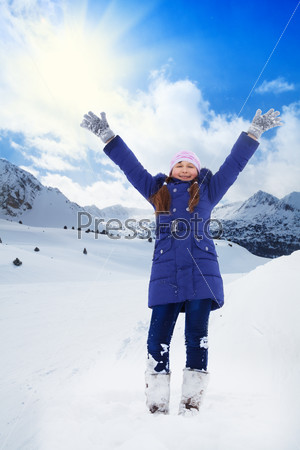Excited girl with lifted hands on snow day