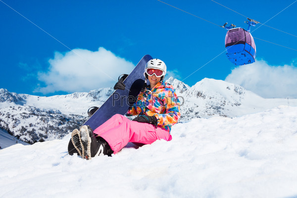 Girl with snowboard on ski resort