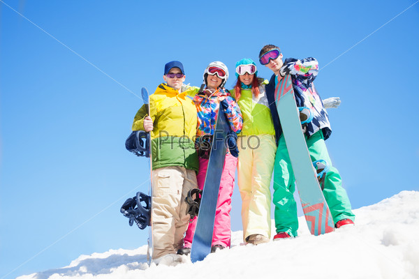 Four happy friends hug and hold snowboards