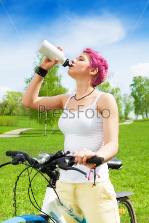 Nice woman biker drinking