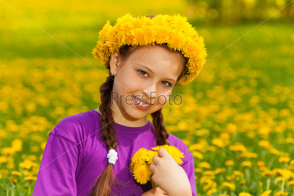 Smiling girl with dandelions