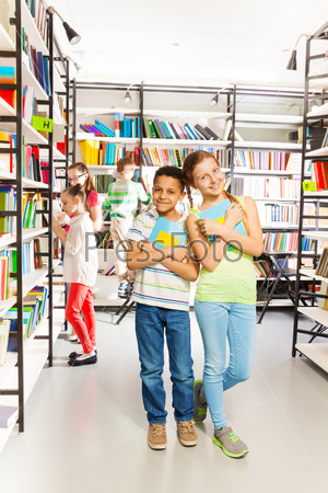 Girl and boy with books stand close in library