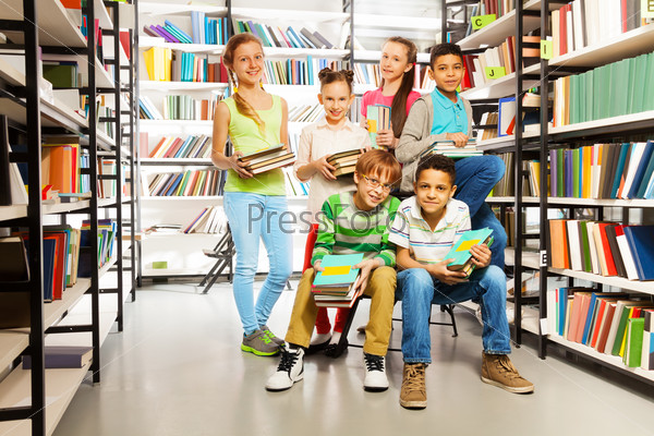 Six pupils in library with piles of books