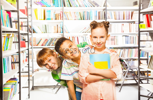 Three children standing in a row with books