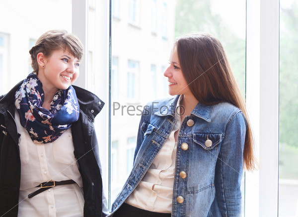 Two happy female students talking near the window