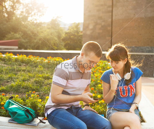Two students or teenagers with mobile phone outdoors