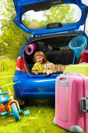 Boy and dog in the trunk waiting