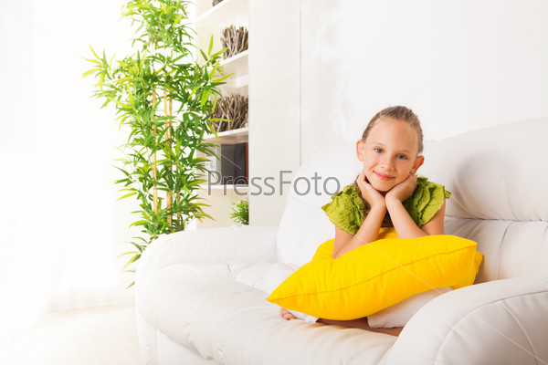 Calm girl sitting on coach with pillow