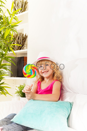 Girl with lollypop at home