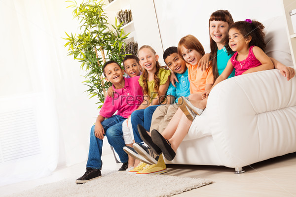 Large group of kids sitting on couch in a row
