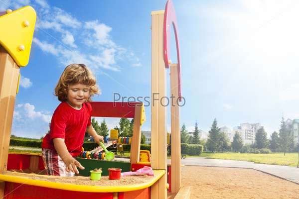 Little boy playing in sandbox